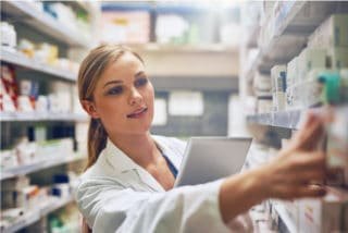 Female pharmacist is searching medicines on shelves