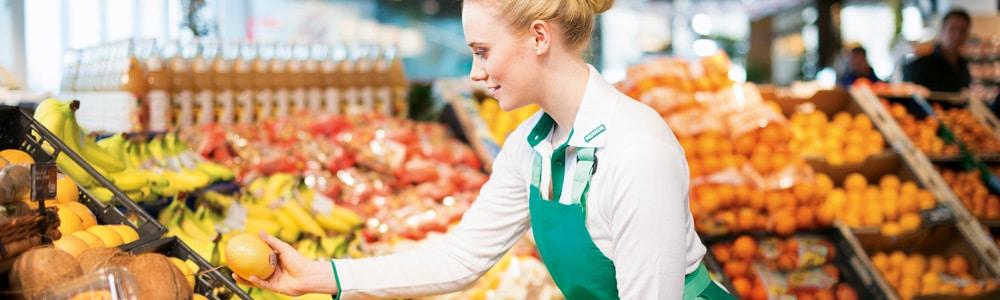 Merkur Mitarbeiterin vor dem Obst- und Gemüseregal - EDI Services für REWE International